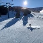 Snowboarder on Enllac Esquirol blue run